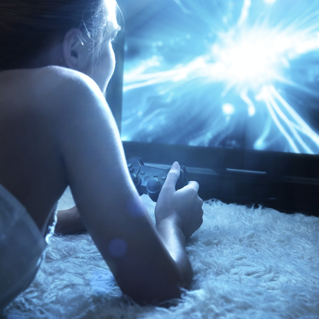 Young woman playing in computer games at night.