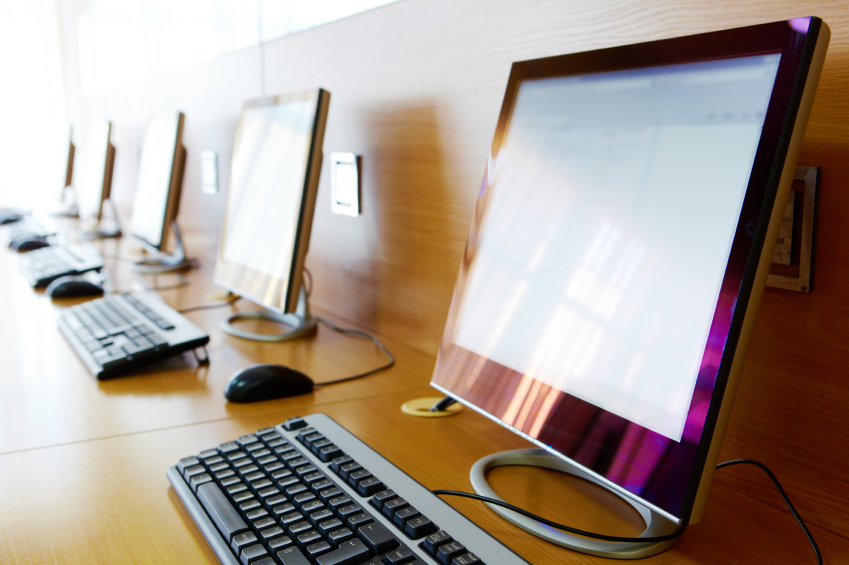 Photo of row of computers in classroom of college or other educational institution
