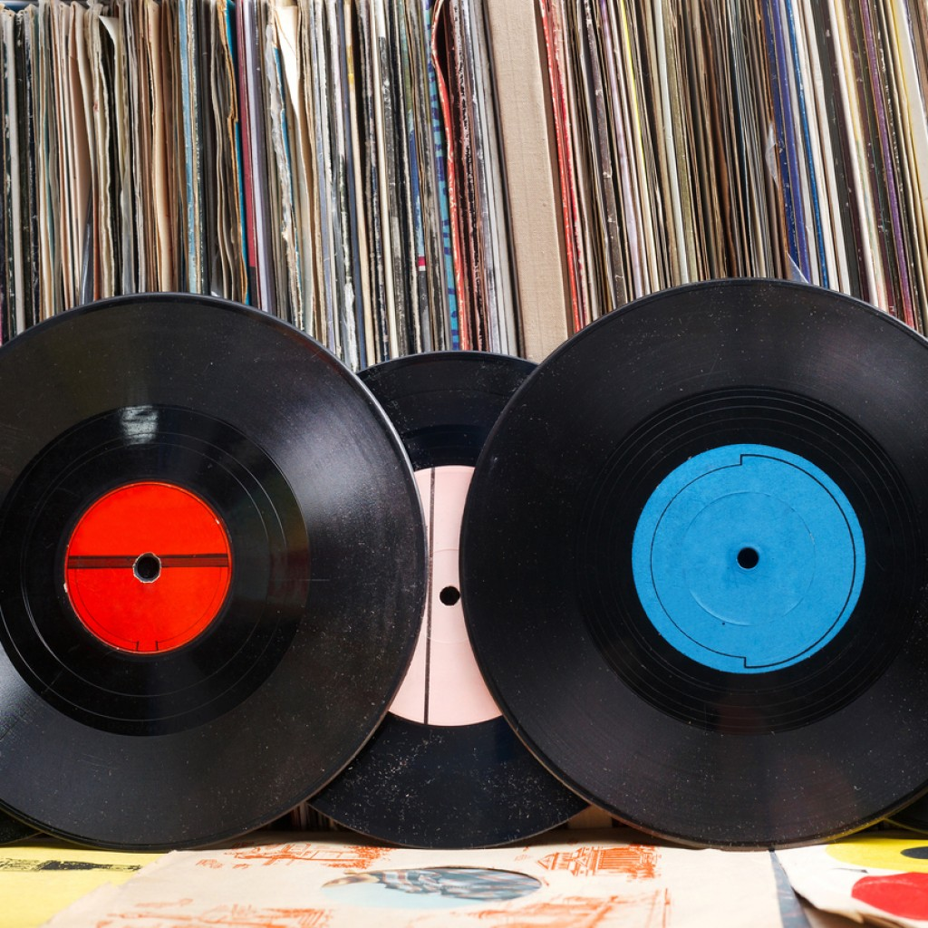 Vinyl record with copy space in front of a collection of albums dummy titles, vintage process
